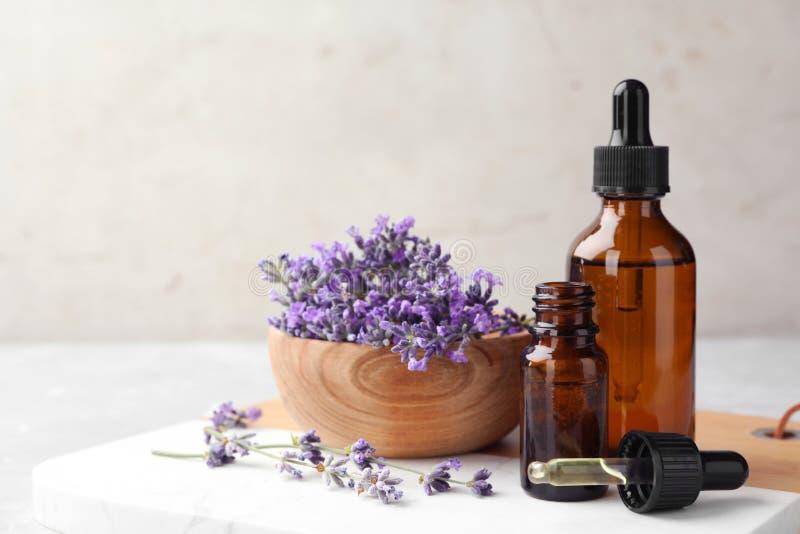De flessen met natuurlijke etherische olie en kom lavendel bloeit op lijst tegen lichte achtergrond stock foto's