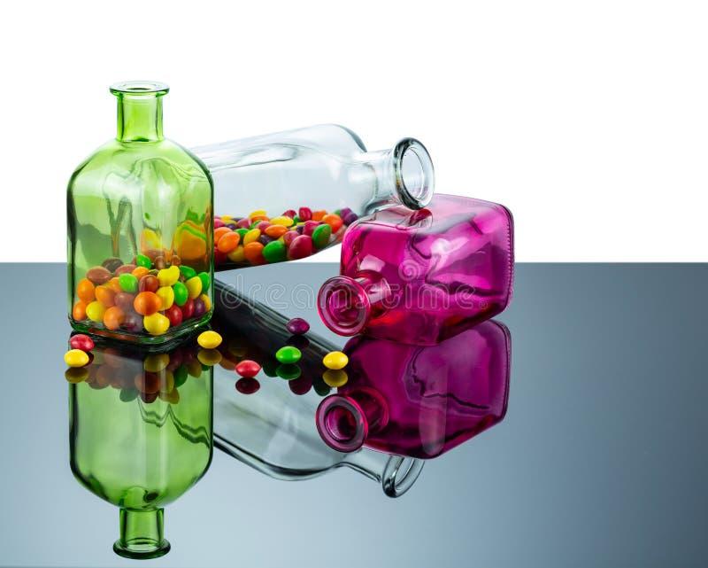 De flessen rechthoekige die vorm van gekleurd die glas wordt met snoepjes wordt gevuld gemaakt worden weerspiegeld in de spiegelo stock foto