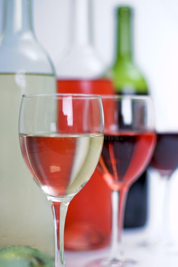 De flessen rood, wit en namen wijn met glazen die in de afstand langzaam verdwijnen toe royalty-vrije stock foto's