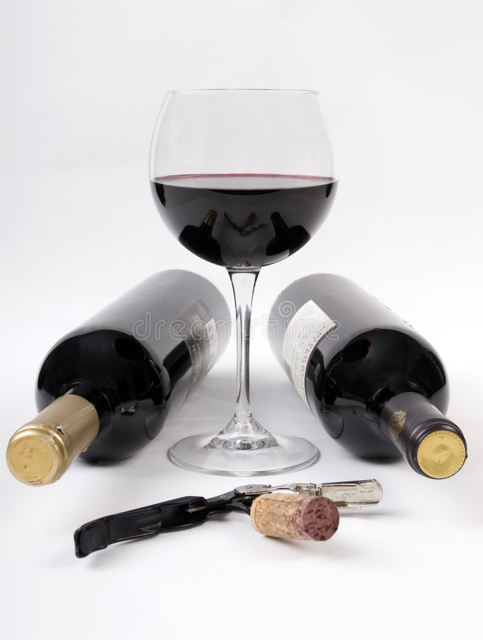 De flessen van de wijn en een glas rode wijn royalty-vrije stock afbeeldingen