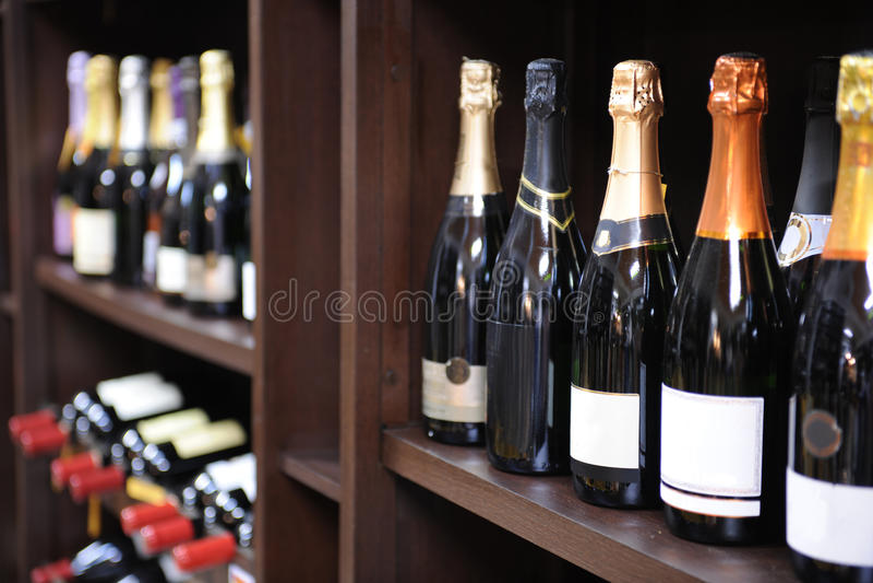 De flessen van de wijn en van de champagne in slijterij stock foto's