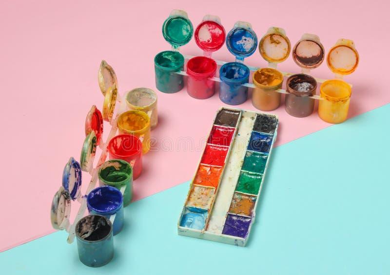 De flessen van gouache en waterverf schilderen voor het trekken op een roze blauwe pastelkleurachtergrond, minimalism stock afbeeldingen