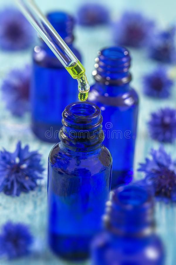 De flessen van het Tranparentglas met dalingen Essentiële vloeistof in druppelbuisje op houten achtergrond met geneeskrachtige bl royalty-vrije stock afbeeldingen
