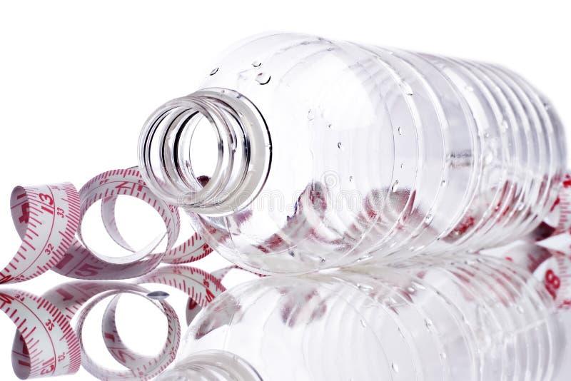 De flessen van het water met meetlint stock afbeelding