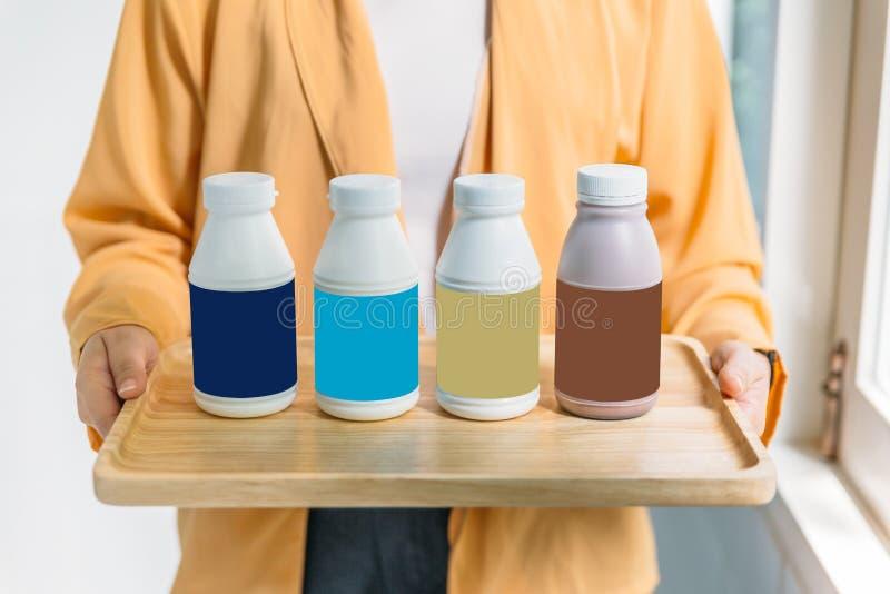 De flessen van de vrouwenholding gepasteuriseerde melk in blauwe, turkooise, gouden en bruine etiketkleur in houten dienblad royalty-vrije stock afbeeldingen