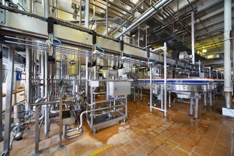 De flessenbeweging van de melk door lange pijpleiding in fabriek royalty-vrije stock afbeelding