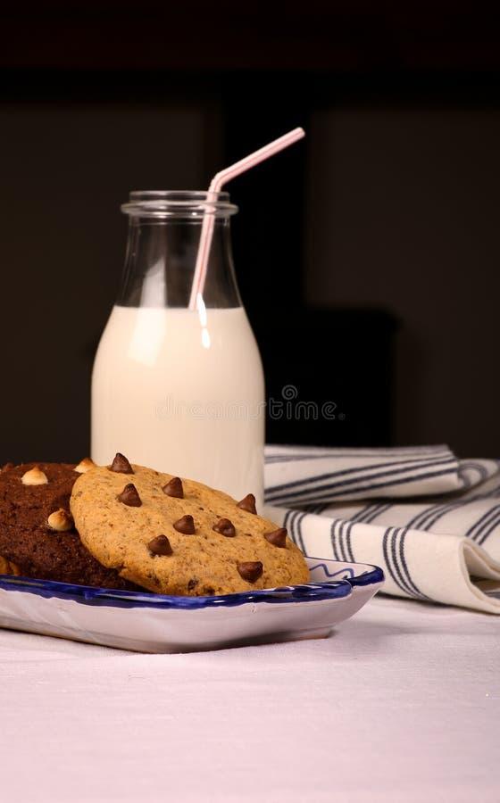 De Flessenstro van chocoladechip cookies ceramic tray milk stock afbeeldingen