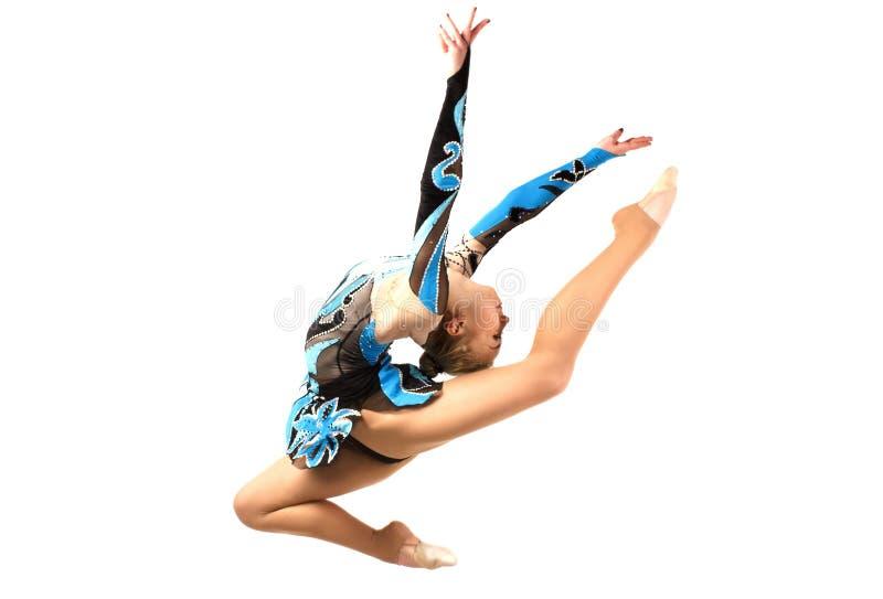 De flexibele jonge turner voert een oefening met uit, het springen stock afbeeldingen