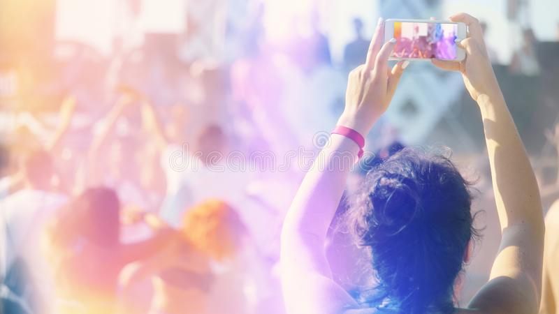 De-fokuserad folkdans på sommarfestivalen eller klubba och en person som antecknar videoen med den smarta telefonen arkivbilder