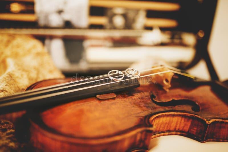 De fonkelende trouwringen liggen op de vioolkoorden stock afbeeldingen