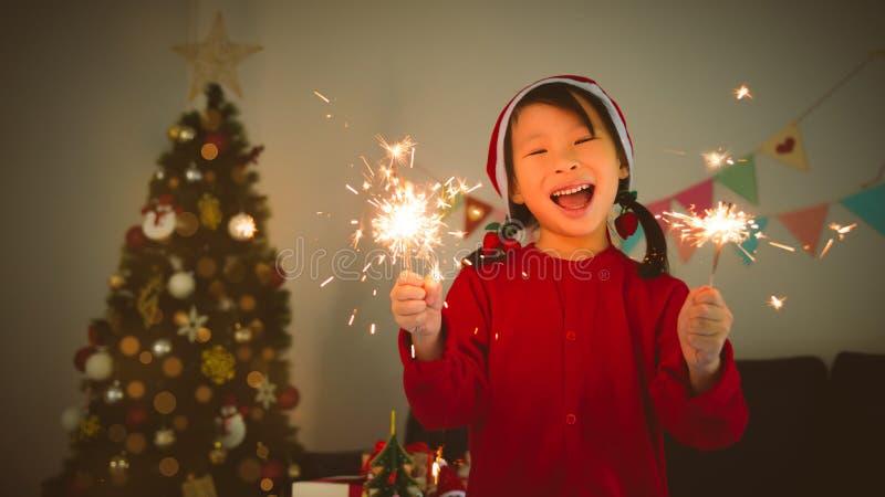 De fonkelingsvuurwerk en glimlach van de meisjesholding in ruimte bij Kerstnacht stock afbeeldingen