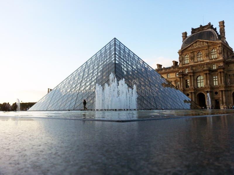 De fontein en de piramide van het Louvremuseum stock afbeelding