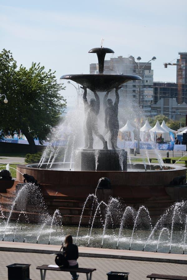 De fontein-mensen houden een grote steenkom waarvan de waterstralen slaan stock fotografie