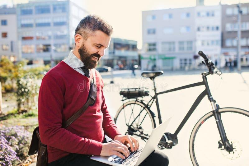 De forens van de Hipsterzakenman met fiets op de manier om in stad te werken, die laptop met behulp van stock afbeeldingen