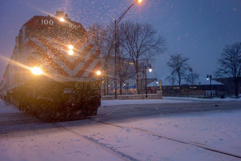 De forenzentrein die van Chicago in de wintersneeuwstorm aankomen stock afbeelding