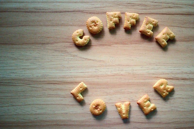 De formulering van het barstjesalfabet op de houten tafel van Koffieover royalty-vrije stock afbeeldingen