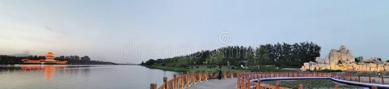 De forntida byggnaderna i avståndet, träna, rockeryen i närheten, sjön royaltyfria bilder