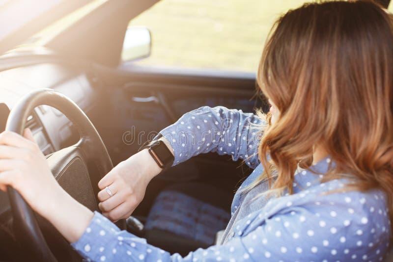 De foto van aantrekkelijk die wijfje controleert tijd op horloge, zit in auto, in opstopping wordt geplakt en laat zijn voor verg royalty-vrije stock foto's