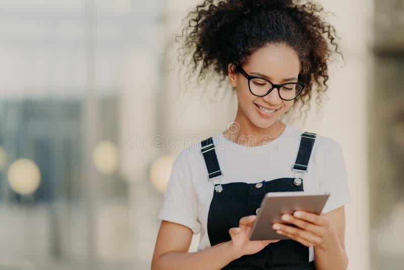 De foto van aantrekkelijk millennial meisje met kernachtig haar, houdt digitale tablet, surfes sociale netwerken, draagt optische royalty-vrije stock foto