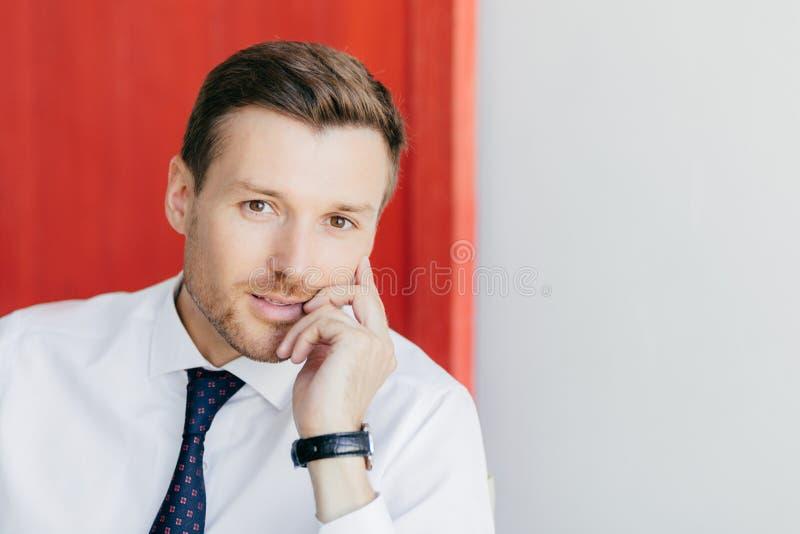 De foto van aantrekkelijke jonge zakenman met zekere uitdrukking houdt kin, gekleed in formeel wit overhemd, heeft horloge op wap stock foto's