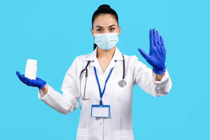 De foto van de charmante jonge vrouw fles van de artsenholding van pillen en het tonen van eindegebaar met overhandigen blauwe ac royalty-vrije stock afbeelding