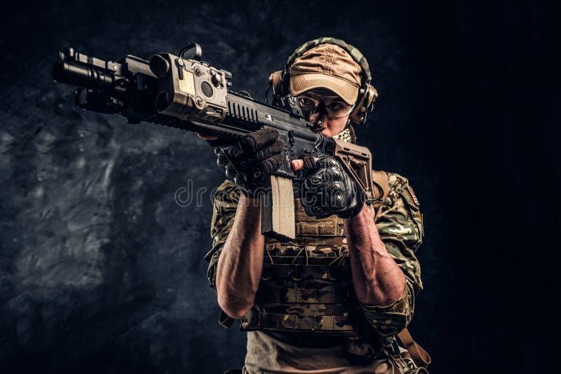 De foto van de close-upstudio tegen een donkere muur De eliteeenheid, speciale krachtenmilitair in camouflage eenvormige holding royalty-vrije stock afbeeldingen