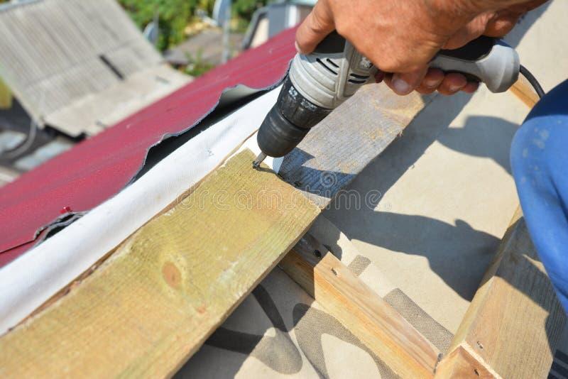 De foto van de dakwerkbouw Roofer met boor installeert houten stralen, bundels, daksparren alvorens de tegels van het metaaldak t stock foto