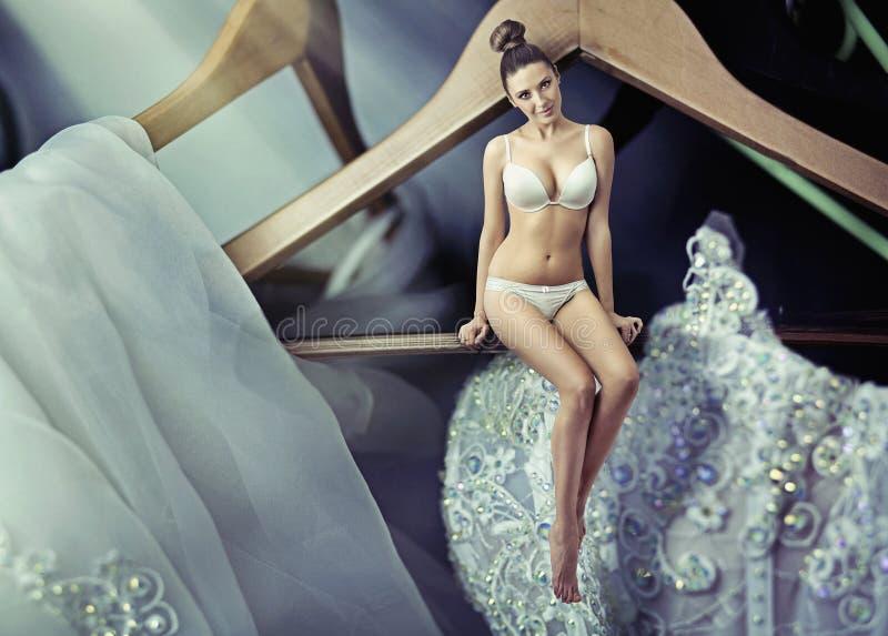 De foto van de kunst van uiterst kleine vrouwenzitting op kledingshanger stock afbeeldingen