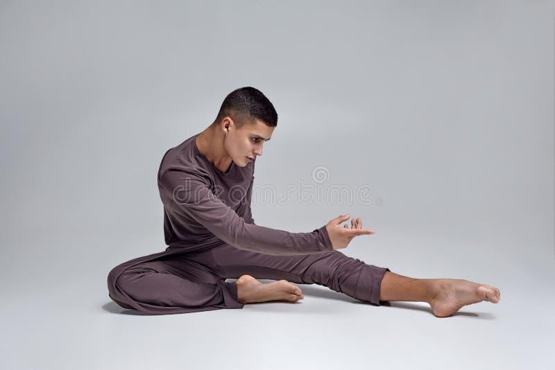 De foto van een atletische mensenballetdanser kleedde zich in een grijze bovenkledij, makend een danselement tegen een grijze ach stock foto