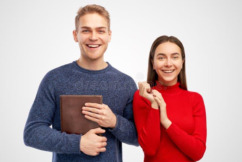 De foto van gelukkig jong wijfje geeft sommige ideeën voor het schrijven van poging aan klasgenoot die blocnote, het werk samen h royalty-vrije stock foto's