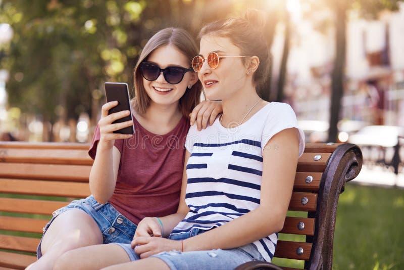 De foto van gelukkig tienersbericht in sociale netwerken, gebruikt slimme telefoon voor vermaak, draagt in zonnebril, stelt op wo royalty-vrije stock foto