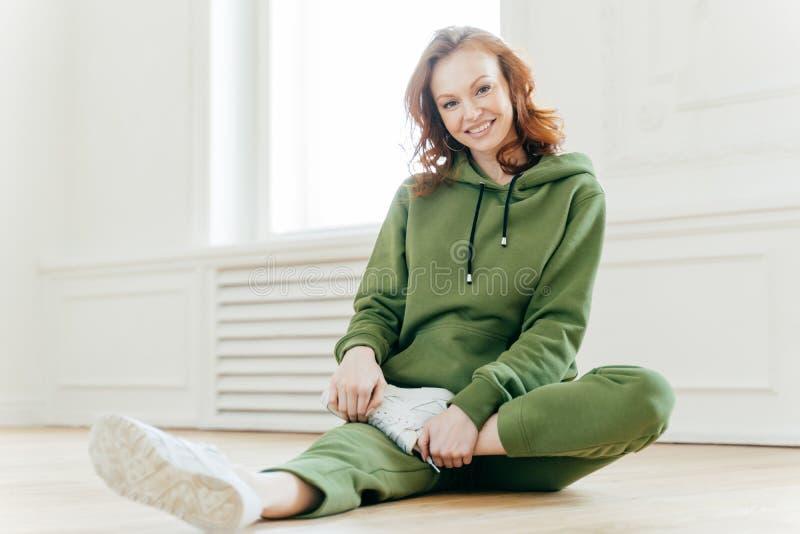 De foto van gelukkige rode haired vrouw in sweatsuit, witte tennisschoenen, neemt rust na training, zit op vloer, uitrekt benen,  royalty-vrije stock afbeeldingen