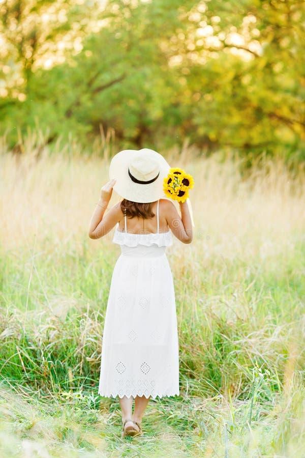 De foto van gemiddelde lengte van een mooi zwanger meisje in een witte kleding die zich bij zonsondergang op een geel gebied bevi royalty-vrije stock foto