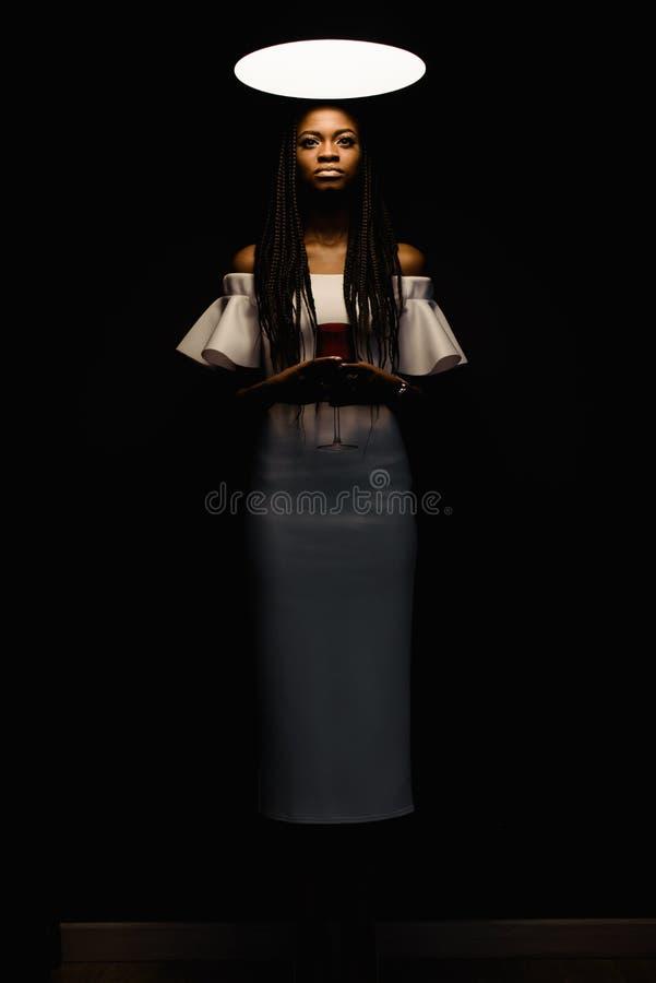 De foto van gemiddelde lengte van de mooie charmante Afrikaanse dame die in modieuze witte kleding de het wijn glas en status hou stock foto