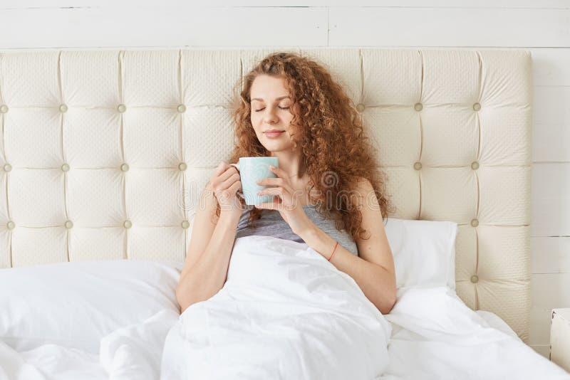 De foto van het charmeren van jonge vrouw met krullend haar, die in bed, het drinken aromatische koffie ii zijn ochtend, kijkt ka stock afbeelding