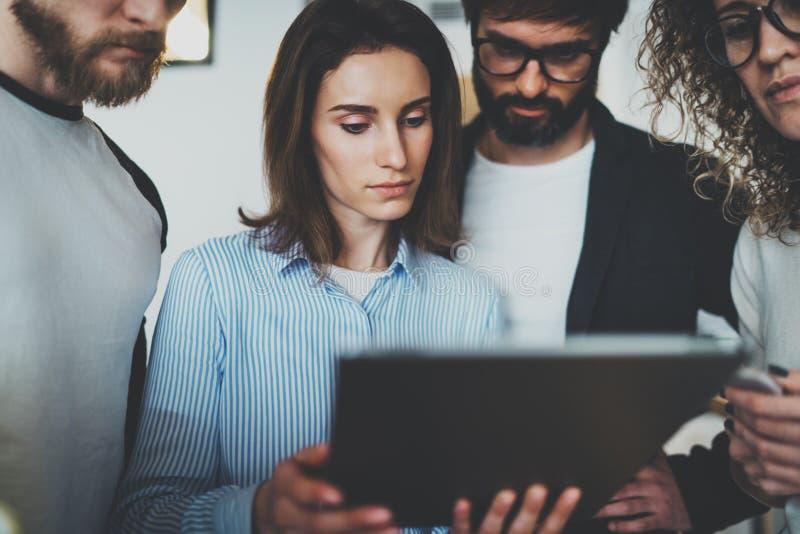 De foto van het Coworkingsteam samen Groep jonge medewerkers die elektronisch aanrakingsstootkussen gebruiken bij moderne bureauz stock afbeelding