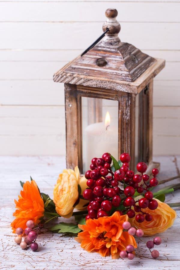 De foto van het de herfststilleven met bloemen in gele kleuren en candl stock fotografie