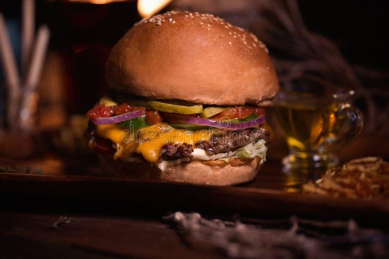 De foto van het hamburgervoedsel Straatvoedsel Verse smakelijke geroosterde die rundvleeshamburger bij barbecue op houten lijst w royalty-vrije stock foto