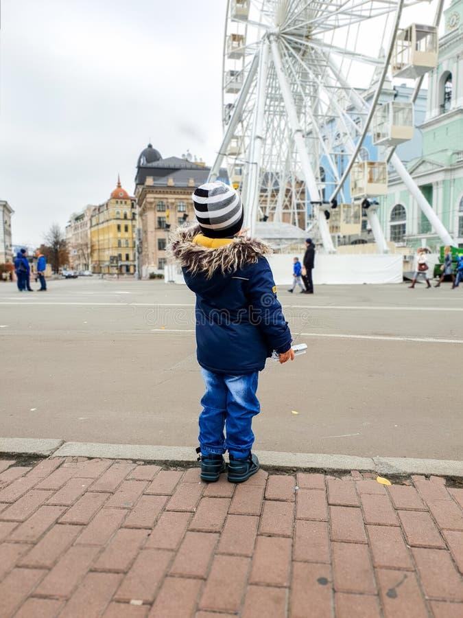 De foto van 3 jaar het oude peuterjongen kijken op hoge ferris rijdt op stadsstraat royalty-vrije stock foto's
