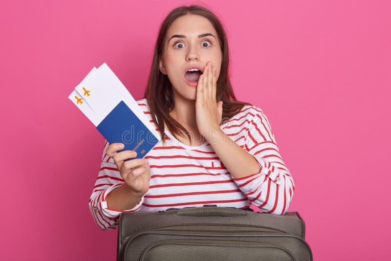 De foto van jong verbaasd meisje met donker recht haar kleedde zich in toevallig overhemd die, die met koffer stellen en paspoort royalty-vrije stock afbeelding
