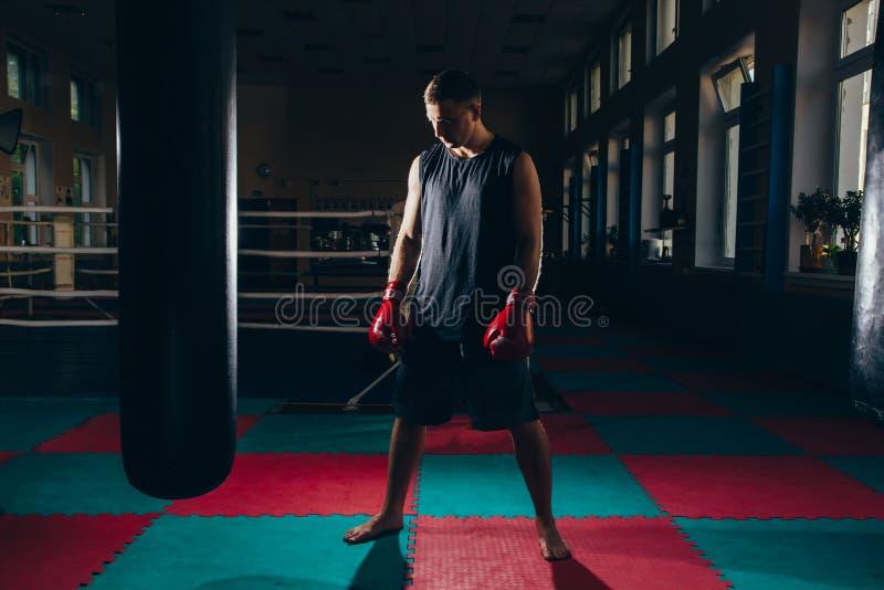 De foto van de jonge sterke bokser van de sportenmens maakt oefeningen in gymnastiek royalty-vrije stock foto's