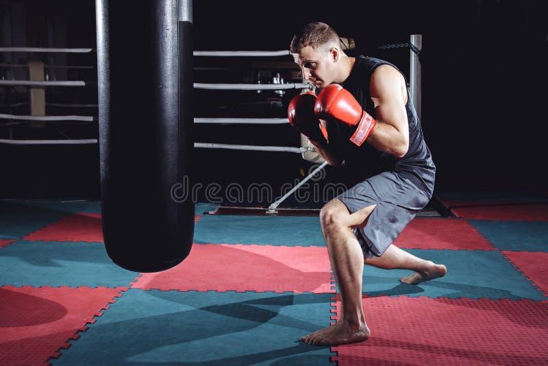 De foto van de jonge sterke bokser van de sportenmens maakt oefeningen in gymnastiek stock foto's