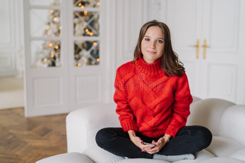 De foto van leuke Europese vrouw heeft donker haar, gekleed in binnenlandse kleren, doorbrengt de winterweekend thuis, zit in lot stock afbeeldingen