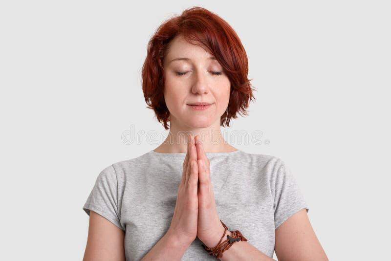 De foto van mooie jonge rode haired vrouw heeft vertrouwen in beter, houdt palmen in het bidden van gebaar, sluit ogen, draagt to stock foto's