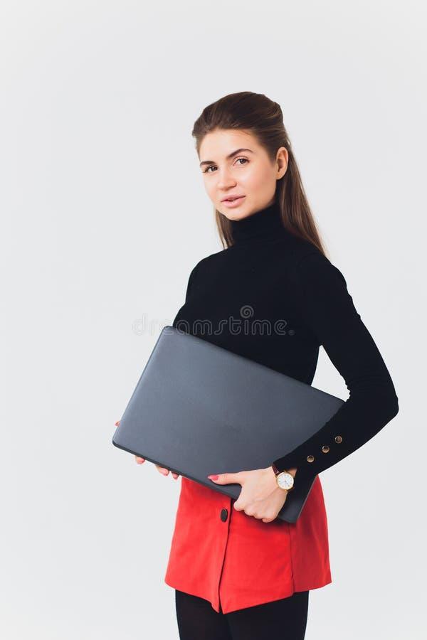 De foto van mooie vrouwenjaren '20 die en computer met benen glimlachen met behulp van kruiste geïsoleerd over witte achtergrond royalty-vrije stock afbeelding
