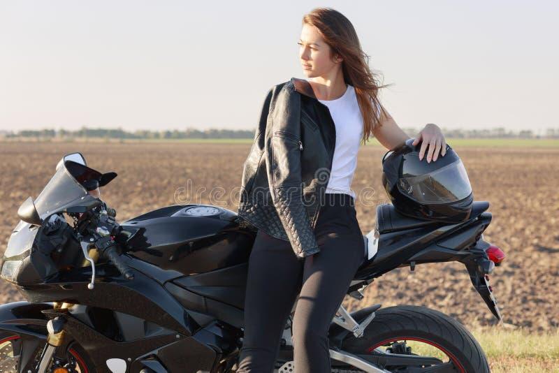 De foto van nadenkend Kaukasisch wijfje houdt van berijdend motor, stelt dichtbij haar snelle fiets, heeft leerjasje op schouder, royalty-vrije stock afbeelding