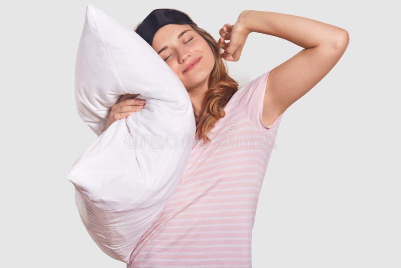 De foto van ontspannen tevreden aantrekkelijke vrouwelijke rek, houdt hoofdkussen, draagt slaapmasker, heeft prettige dromen, hee royalty-vrije stock afbeeldingen