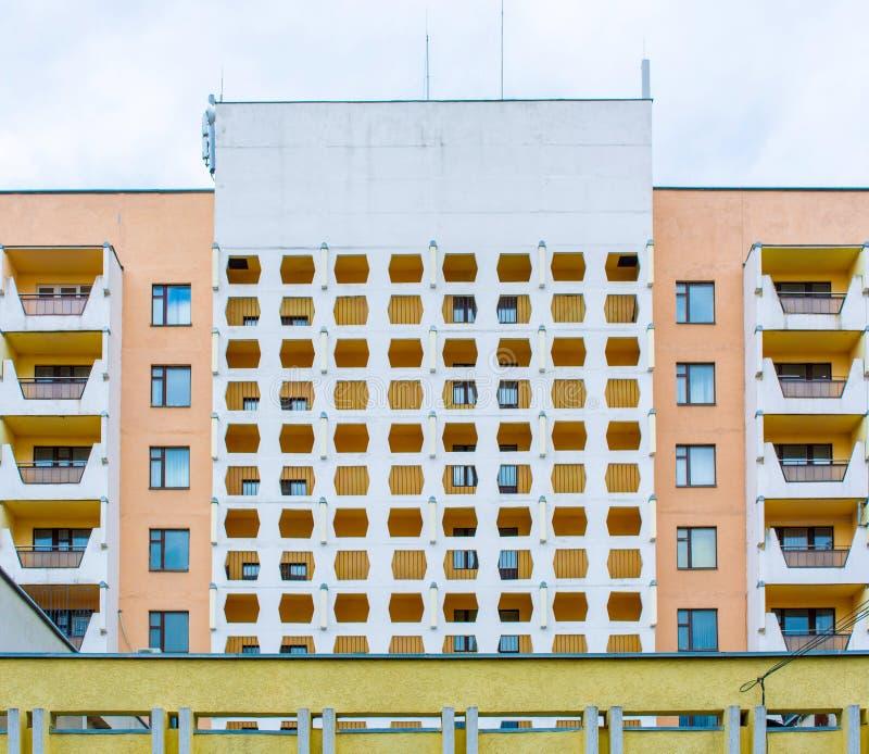 De foto van oranje wit modern flatgebouw met netwerk ziet eruit stock foto's