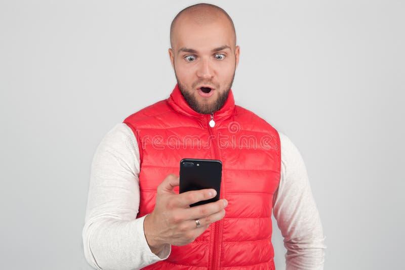 De foto van overweldigd mannetje leest sms-bericht met verraste uitdrukking, houdt celtelefoon, te weten komt iets schokken, verb stock afbeeldingen