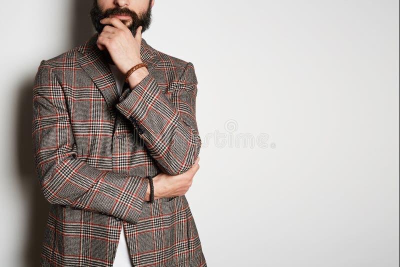 De foto van peinzend hipstermodel stelt in toevallig jasje en leeg wit de zomerkatoen van de t-shirtpremie, op witte achtergrond stock fotografie
